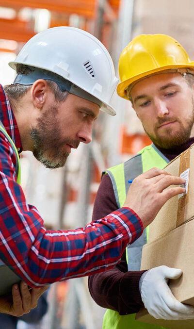 Side view portrait of two shipping workers marking cardboard box for delivery  in modern warehouse